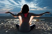 Girl With Long Hair Sitting On The Beach In Lotus Pose Embracing Last Sunset Light With Open Arms poster