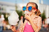 stock photo of candy cotton  - Girl eating cotton candy - JPG