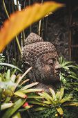 Stone Buddha Head Close-up. Handmade Carved Buddha Statue In Balinese Garden As Decoration. poster