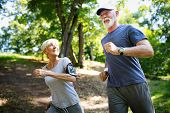 Mature Or Senior Couple Doing Sport Outdoors, Jogging In A Park poster