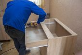 Assembly Of Kitchen Furniture, Man Gathers Furniture With His Back Wrapped, Assembling Drawers Insta poster