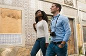 Multiethnic Couple Of Tourists Going Sightseeing. Young Man And Woman With Camera Walking In Old Cit poster