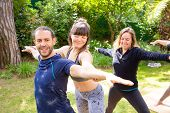 Trainer Helping Man In Yoga Practice. Smiling Young Woman Helping Cheerful Man In Yoga Practice Outd poster