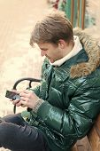 Hipster Use Smartphone On Winter Day. Man Handsome Hold Smartphone. Man Unshaven Wear Warm Jacket An poster