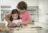 Asian grandmother and granddaughter making sushi roll