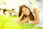 Summer girl in grass smiling happy. Lifestyle image of beautiful young woman in summer dress lying j