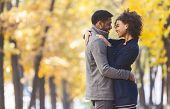 Love And Romance Concept. Sweet Black Couple Hugging And Looking At Each Other, Autumn Trees Backgro poster
