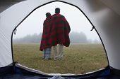 Indian couple wrapped in blanket at campsite