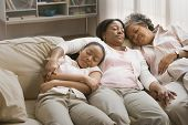 Three generations of African women sleeping on sofa