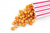 Caramel corn spilling out of striped container onto white surface.