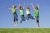 stock photo of children group  - happy group of kids children twins youth jumping for joy at summer camp - JPG