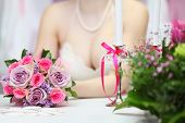 decollete of young bride wearing white dress, which sits at table with candles and holds bouquet of
