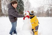 Little Boy With His Father Building Snowman In Snowy Park. Active Outdoors Leisure With Children In  poster