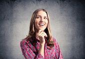 Smiling Young Woman Touching Chin And Looking Upward. Emotional Beautiful Girl Has Pleasant Facial E poster