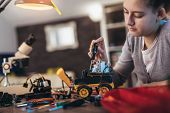 Girl Constructs Technical Toy. Technical Toy On Table Full Of Details poster