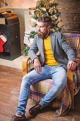 Home Is Best Place. Man Bearded Hipster Relax Sit Armchair Near Christmas Tree. Feel Like Home. Man  poster