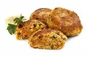 Salmon fishcakes or patties, with lemon and parsley, isolated on white background.