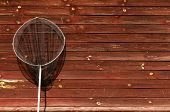 Metallically, A Fishing Net With A Black Net Stands Leaned Against An Old Wooden Wall Of A House. Th poster