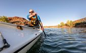 Senior male paddler is paddling an expedition decked canoe on a mountain lake in Colorado, POV from  poster