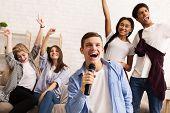 Playing Karaoke. Teenagers Having Fun At Home Party, Singing Songs And Dancing poster