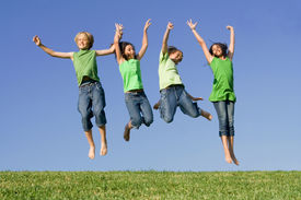 image of children group  - happy group of kids children twins youth jumping for joy at summer camp - JPG