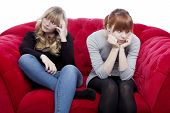 Young Beautiful Blond And Red Haired Girls Are Bored And Depressed On Red Sofa In Front Of White Bac