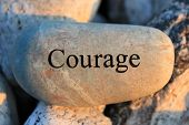 stock photo of reinforcing  - Positve reinforcement word Courage engrained in a rock - JPG