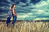 Romantic young couple in casual clothes standing together in a wheat field on a background of the st