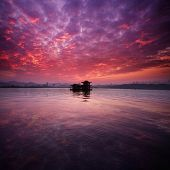ancient boat on lake with sunset