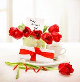 Image of fresh red tulips bouquet in beautiful vase with greeting postcard on the table, little whit