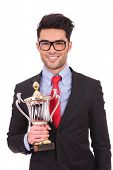 young business man holding a trophy and smiling proudly to the camera
