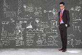 full length picture of a young business man standing with hands in pockets in front of a blackboard full of sketches and charts