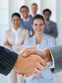 Geschäftsleute Händeschütteln mit lächelnden Business Team dahinter