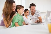 Happy family using a laptop in kitchen