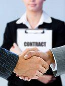 Geschäftsleute Händeschütteln mit Frau Vertrag hinter ihnen halten