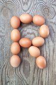 Una letra R de los huevos de Pascua. En una textura de madera.