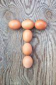Una letra T de los huevos de Pascua. En una textura de madera.