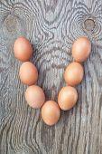 Una letra V de los huevos de Pascua. En una textura de madera.