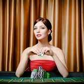 stock photo of roulette table  - Portrait of female gambler sitting at the roulette table with chip in hand - JPG