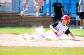 stock photo of ten  - Youth baseball player sliding in at home - JPG