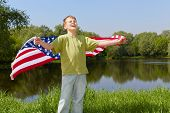 Boy in green t-shirt stands on bank of pond with eyes closed against the sun and holds unfolded flag