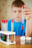 Boy in blue t-shirt sits at table with chemical reagents and holds test tube in his hand, focus at f