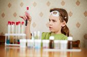 Girl in green t-shirt looks anxiously at test tube with specimen in her hand
