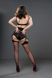 stock photo of cheeky  - cheeky sexy rear view of retro model in black lingerie  - JPG