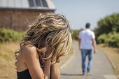foto of crying  - Unhappy woman in focus crying and angry man leaving on the background after quarrel - JPG