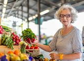 senior woman choosing vegetable at the market