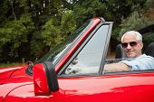 Cheerful handsome man enjoying his red convertible on a bright day