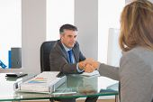 Serious mature businessman shaking the hand of a blonde interviewee in office