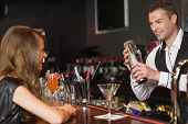 image of bartender  - Handsome bartender serving cocktail to beautiful woman in a classy bar - JPG