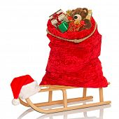 Santa's sack full of gift wrapped Christmas presents and toys including a handmade bear on a wooden